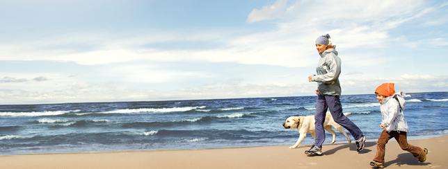 Kind Frau und Hund joggen am Strand